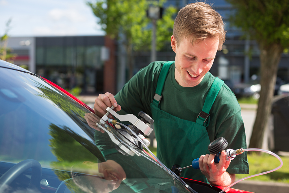 image of a man repairing a windscreen using specific tool and gauge